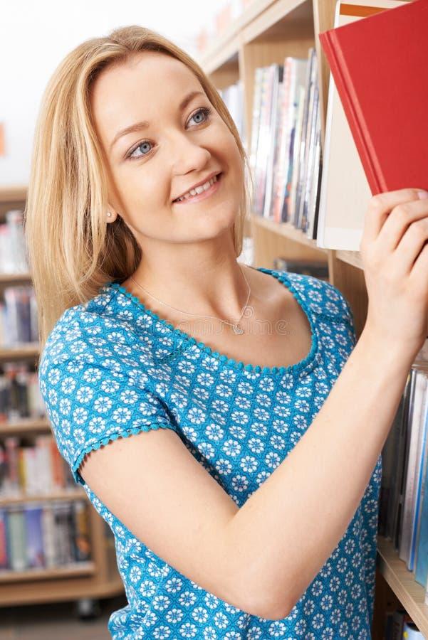 Étudiante étudiant dans la bibliothèque photos stock