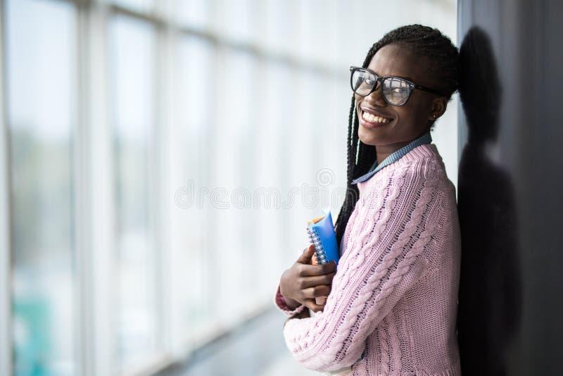 Étudiante afro-américaine de jeune beauté en verres tenant des carnets dans le hall moderne d'université images libres de droits