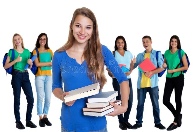 Étudiante allemande heureuse avec des livres et groupe d'étudiants photos stock