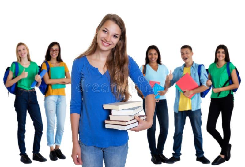 Étudiante allemande mignonne avec des livres et groupe d'étudiants photos stock