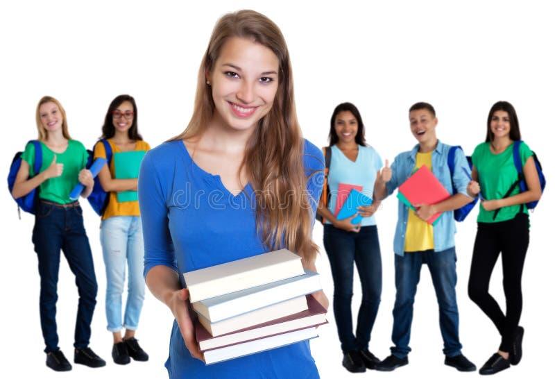Étudiante allemande riante avec des livres et groupe d'étudiants images libres de droits