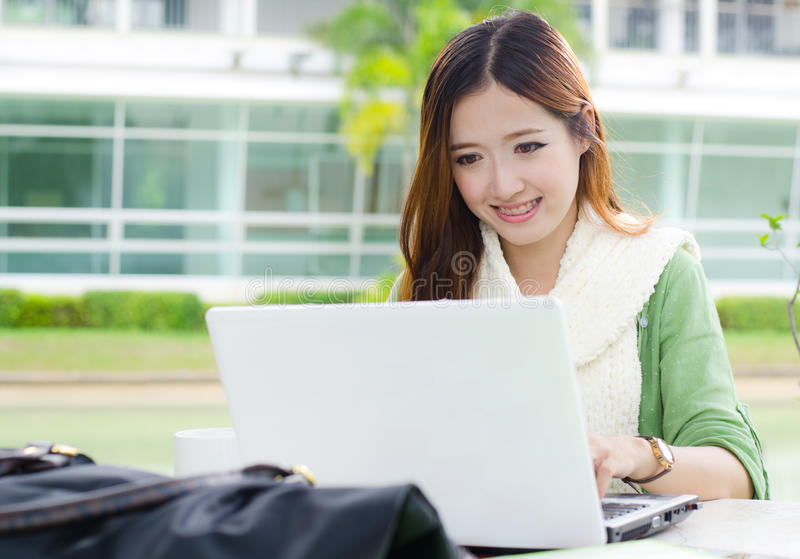 Étudiante asiatique avec l'ordinateur portable d'ordinateur image stock