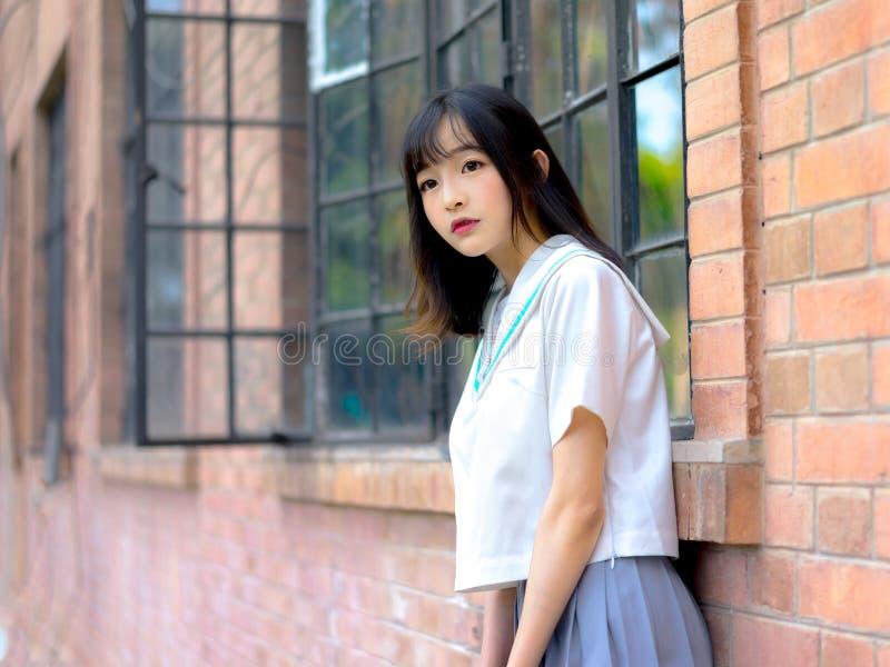 Étudiante asiatique dans l'uniforme scolaire apprenant dans la salle de classe image libre de droits