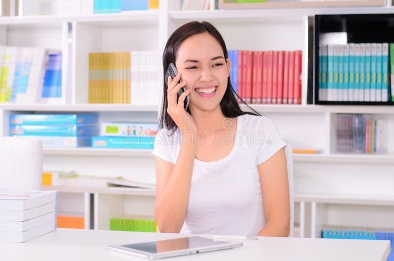 Étudiante asiatique heureuse avec le téléphone images stock
