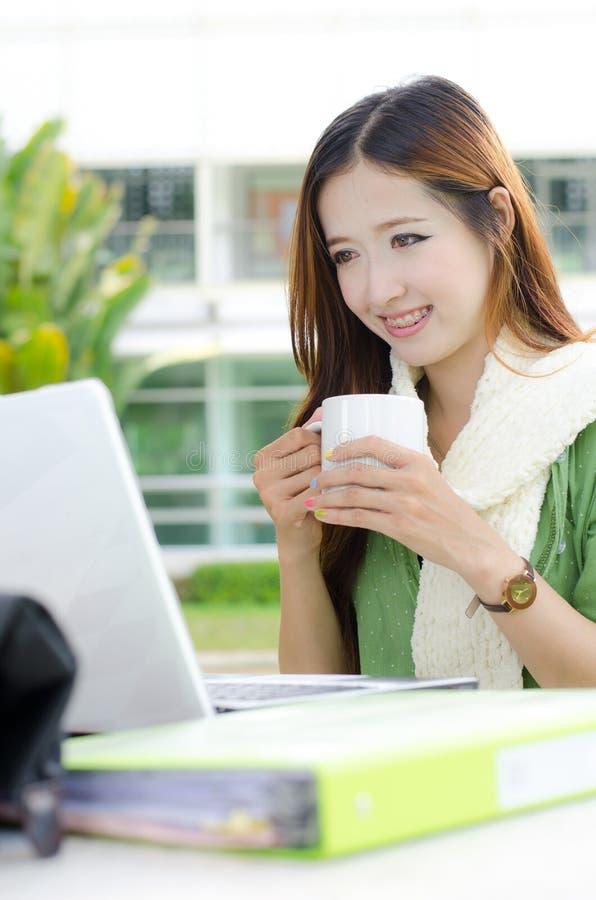 Étudiante asiatique souriant avec la tasse de café image stock