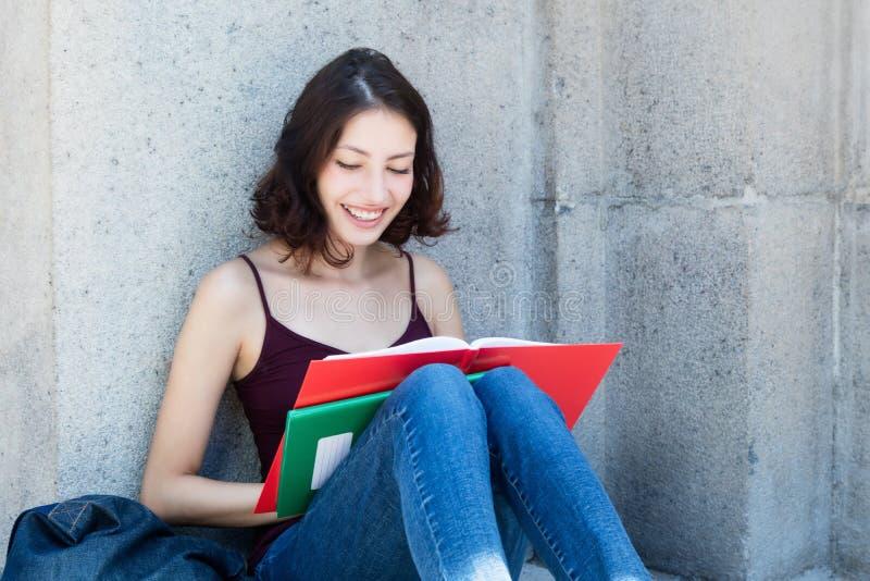 Étudiante avec le long livre de lecture de cheveux foncés photos stock