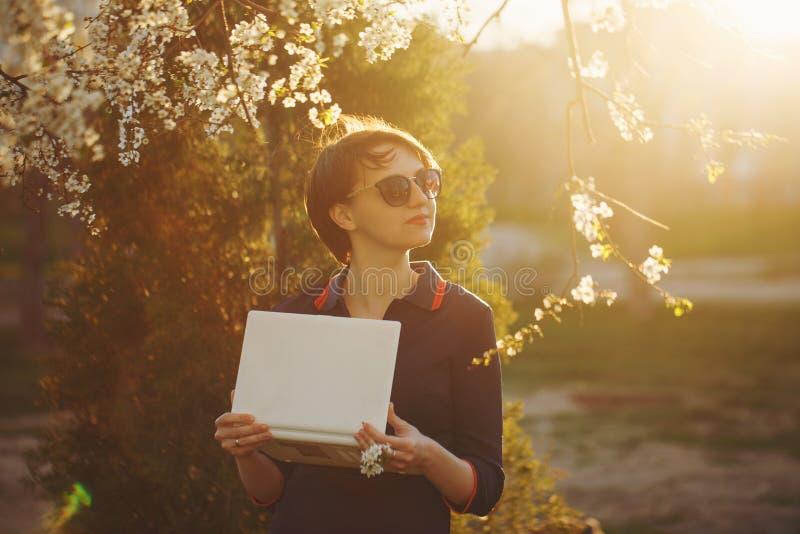 Étudiante avec un ordinateur portable en parc Portrait photo stock