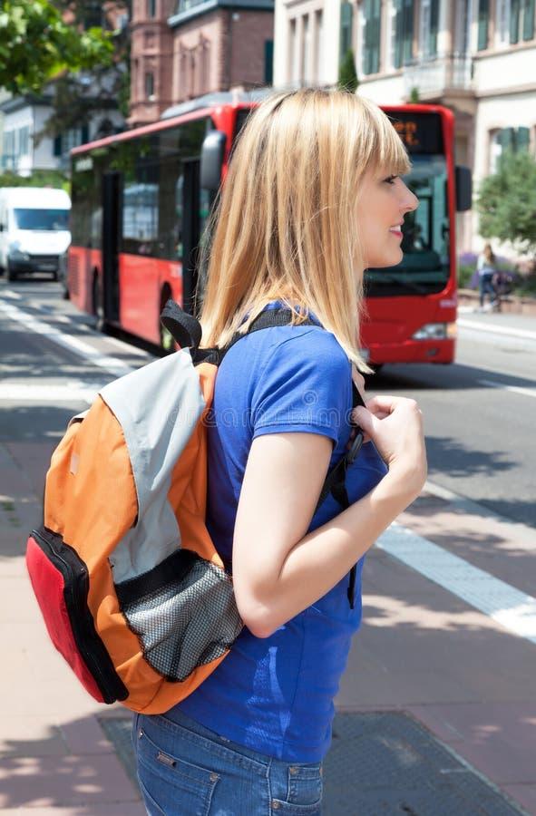 Étudiante blonde attendant l'autobus images libres de droits