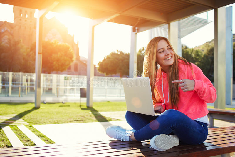 Étudiante blonde avec du charme indiquant l'ordinateur portable ouvert photographie stock libre de droits