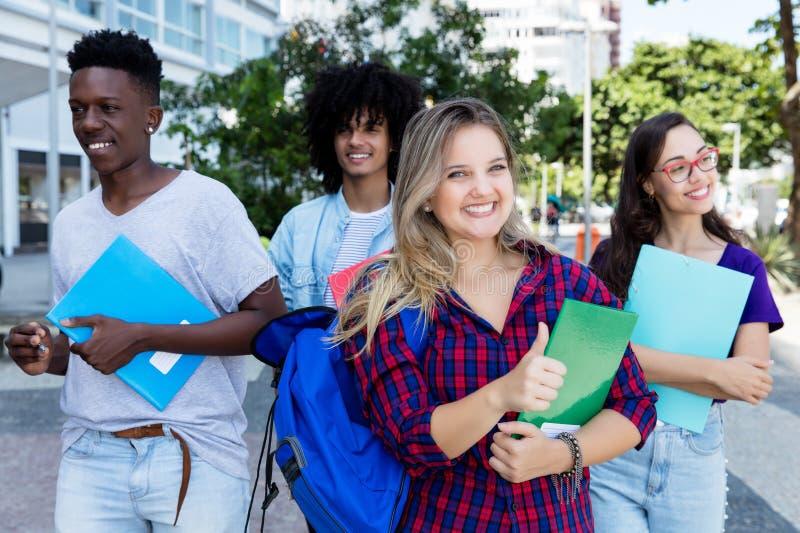 Étudiante blonde réussie avec le groupe d'étudiants d'internternational images stock