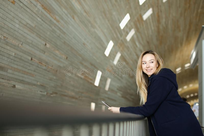 Étudiante blonde se tenant avec le smartphone moderne à l'arrière-plan lumineux monophonique photos stock