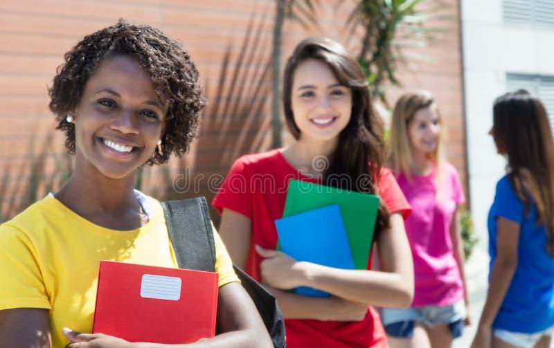 Étudiante d'afro-américain avec d'autres étudiants internationaux extérieurs dans la ville photo libre de droits