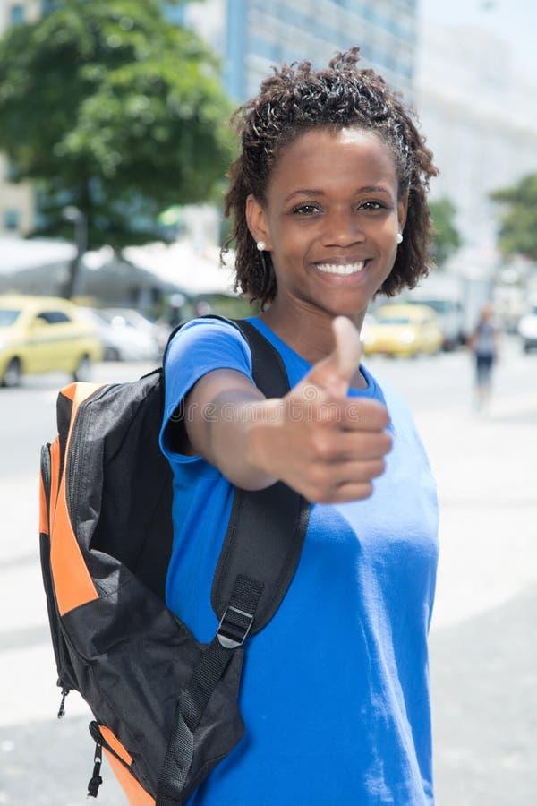 Étudiante d'afro-américain dans la ville montrant le pouce  images stock