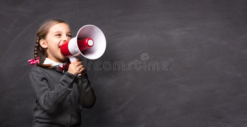 Étudiante d'enfant Shouting Through Megaphone au tableau noir photographie stock