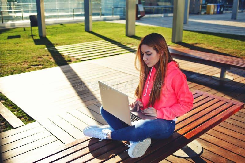 Étudiante de cheveux blonds dactylographiant sur le clavier d'ordinateur portable se reposant au campus image stock