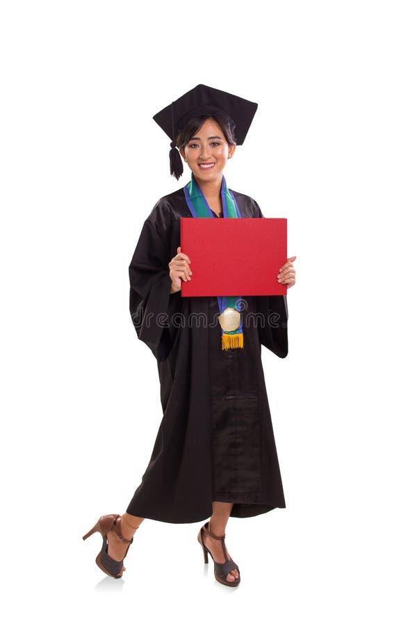 Étudiante de graduation heureuse avec une plaquette rouge, plein corps PO photo libre de droits