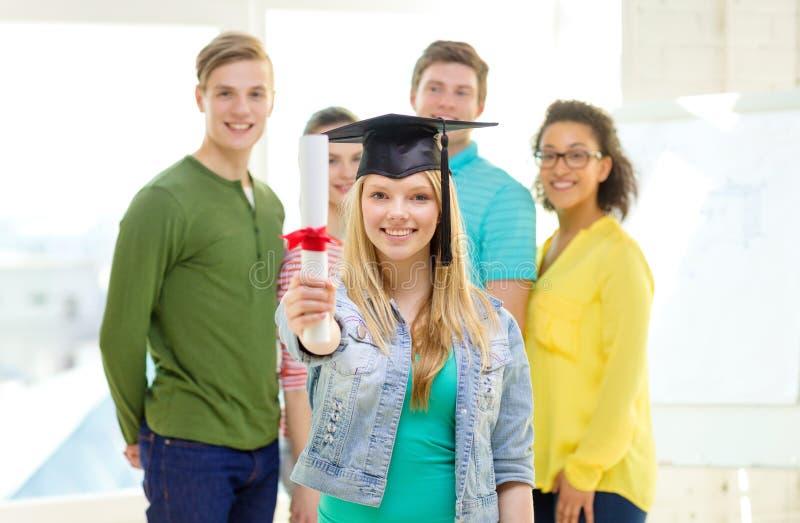 Étudiante de sourire avec le diplôme et le coin-chapeau image libre de droits
