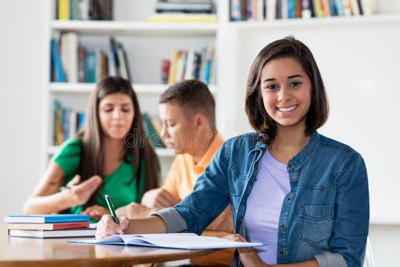 Étudiante espagnole futée avec le groupe d'apprendre des étudiants photos stock