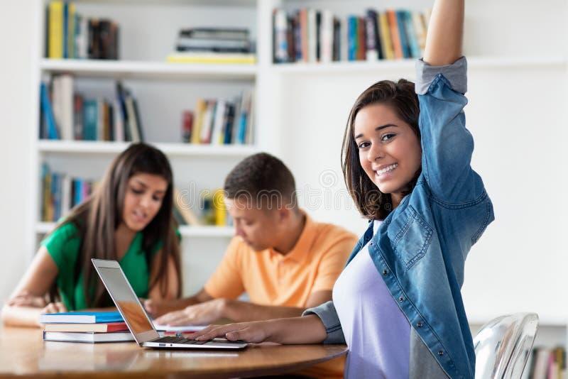Étudiante espagnole heureuse avec le groupe d'apprendre des étudiants image stock