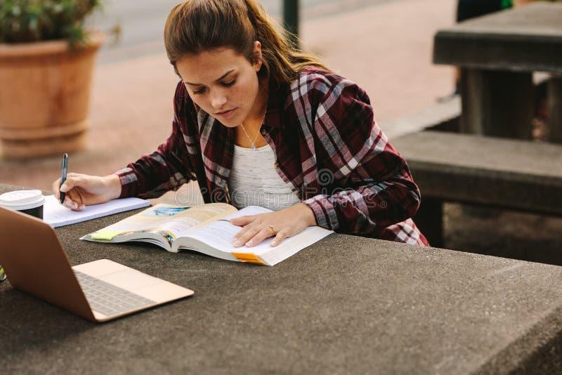 Étudiante faisant des notes au campus d'université image stock