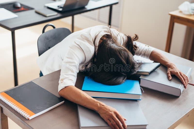 Étudiante fatiguée dormant sur le visage et les mains de bureau sur des livres photographie stock