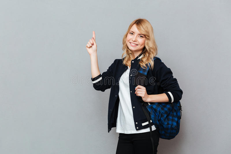 Étudiante gaie de jeune dame avec le pointage de sac à dos images stock