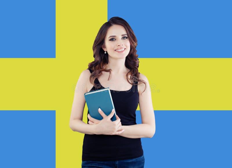 Étudiante heureuse avec la couverture de livre vide sur le fond de drapeau de la Suède Sourire de fille photos stock