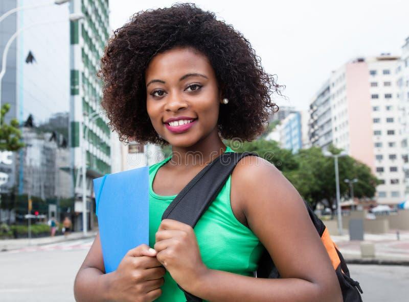 Étudiante heureuse d'Afrique dans la chemise verte dans la ville photos libres de droits