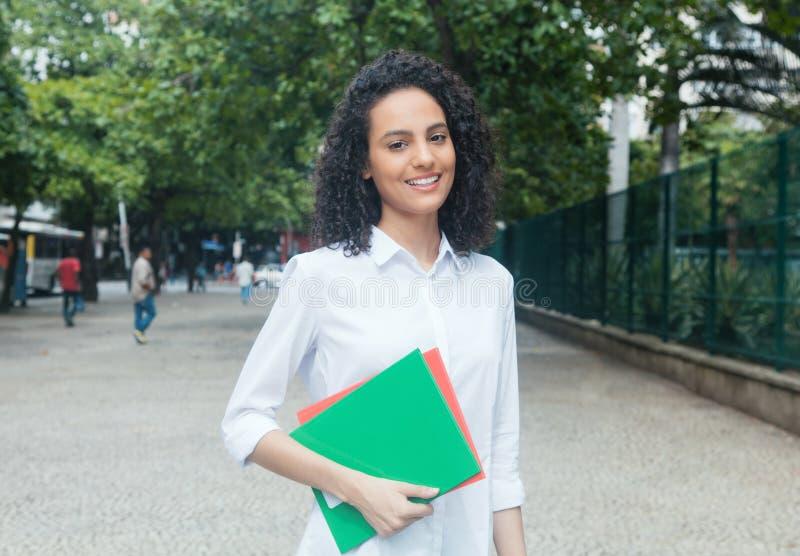 Étudiante latine riante avec les cheveux bouclés et la chemise blanche photographie stock