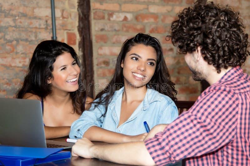 Étudiante latino-américaine heureuse apprenant avec d'autres étudiants photo libre de droits