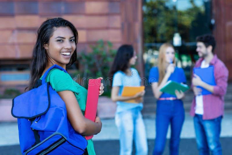 Étudiante latino-américaine heureuse avec le groupe d'étudiants image stock
