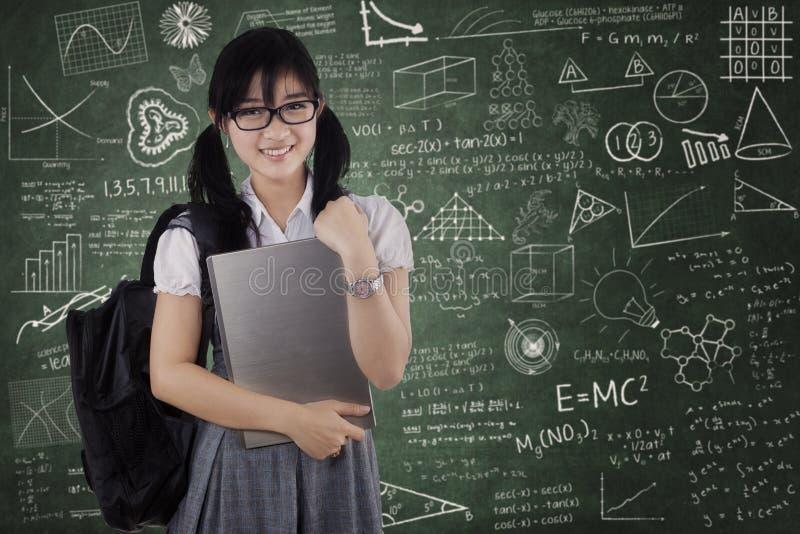 Étudiante mignonne tenant l'ordinateur portable dans la classe photos libres de droits