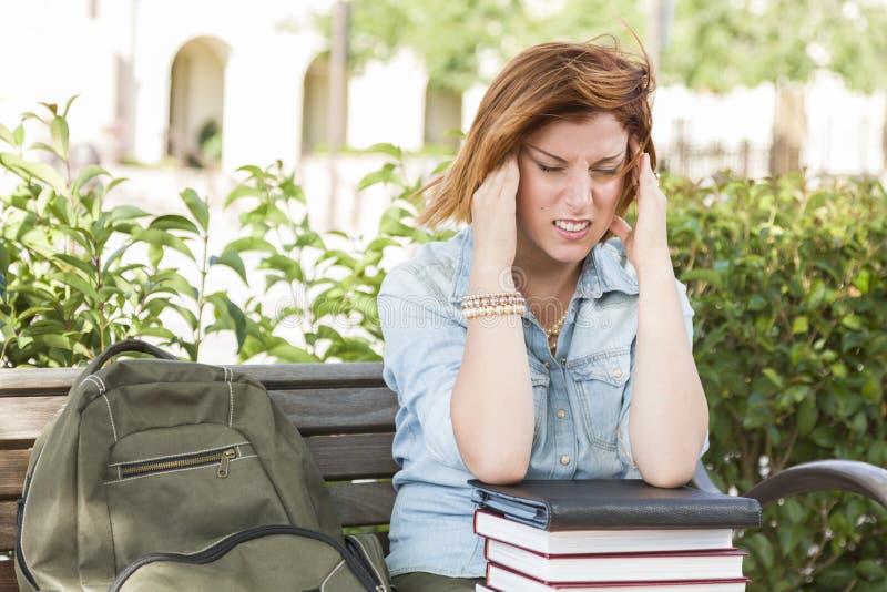 Étudiante Outside avec le mal de tête se reposant avec les livres et le dos image stock