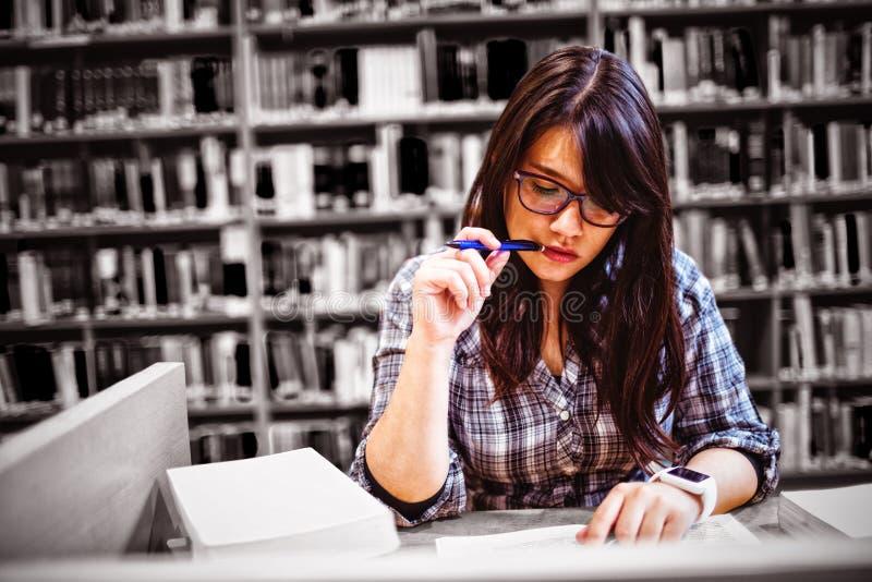 Étudiante regardant des notes dans la bibliothèque images libres de droits