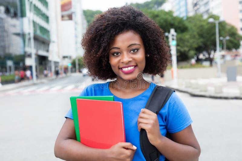 Étudiante riante d'Afrique dans la chemise bleue dans la ville image libre de droits