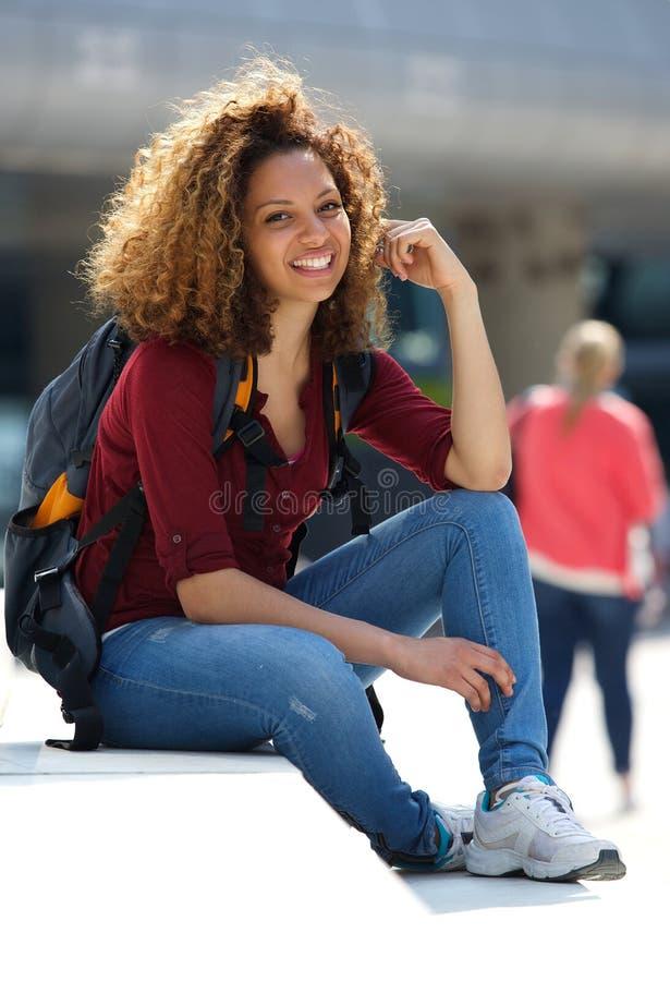 Étudiante s'asseyant dehors avec le sac photo libre de droits