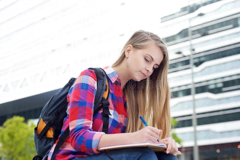 Étudiante s'asseyant dehors avec le sac et écrivant dans le livre photo libre de droits