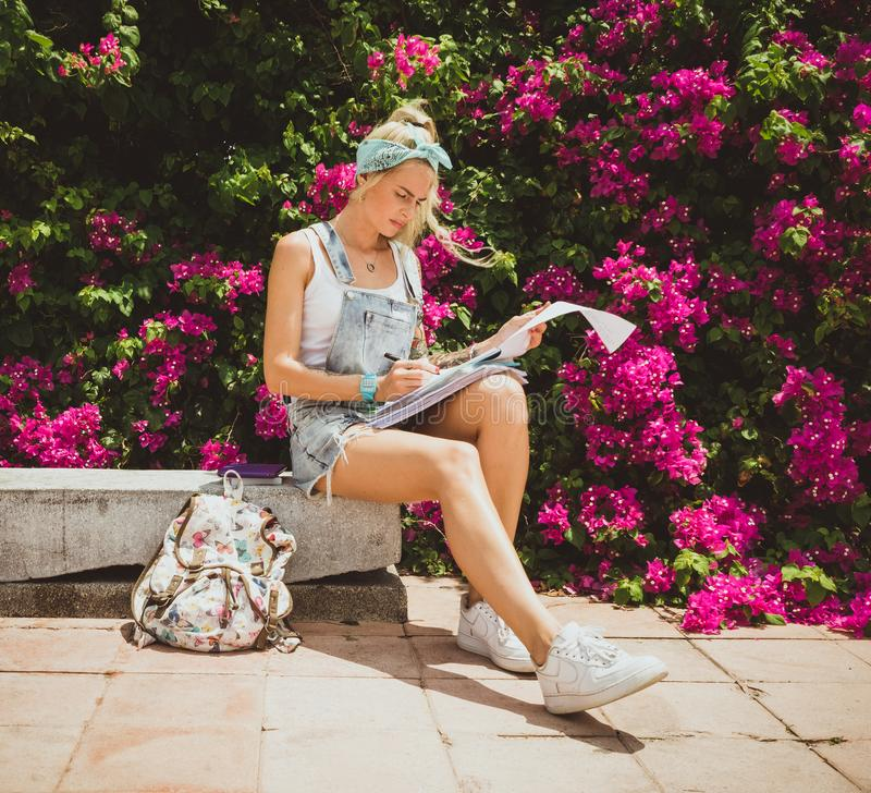 Étudiante s'asseyant en parc d'été et faisant le travail Style moderne de la fille Modèle avec des tatouages image stock
