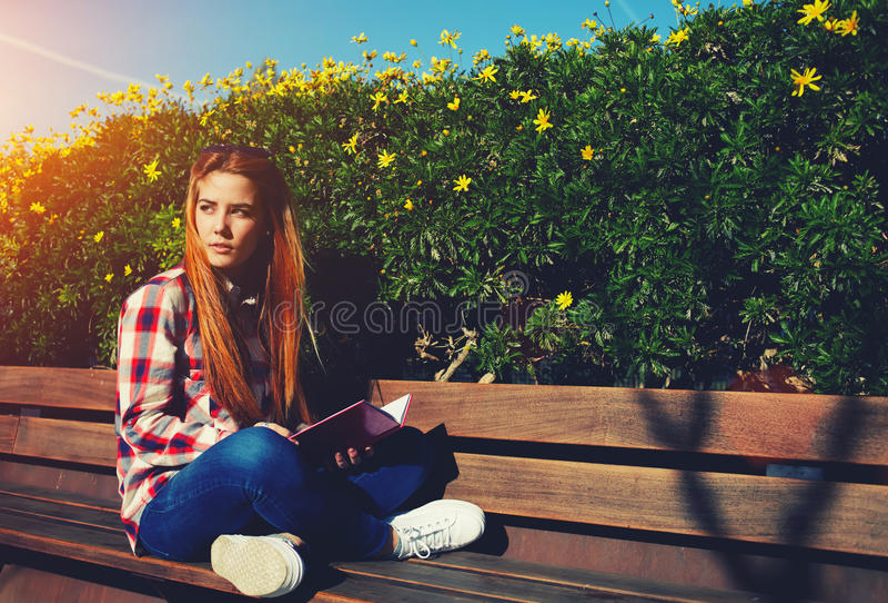 Étudiante s'asseyant sur le banc en bois au campus images stock