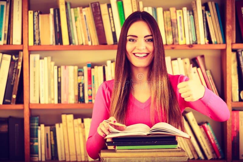 Étudiante satisfaite à la bibliothèque universitaire photo stock