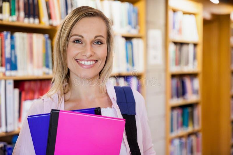 Étudiante tenant des manuels dans la bibliothèque images stock