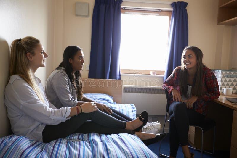 Étudiantes détendant dans la chambre à coucher du logement de campus images libres de droits