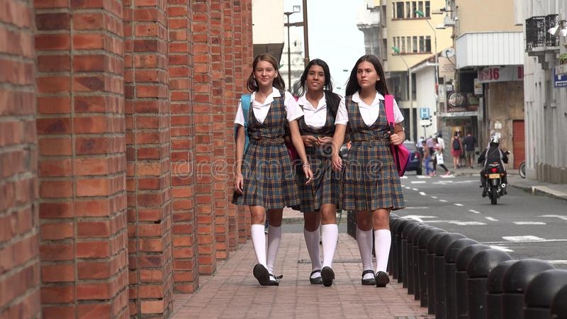 Étudiantes marchant sur le trottoir photos stock