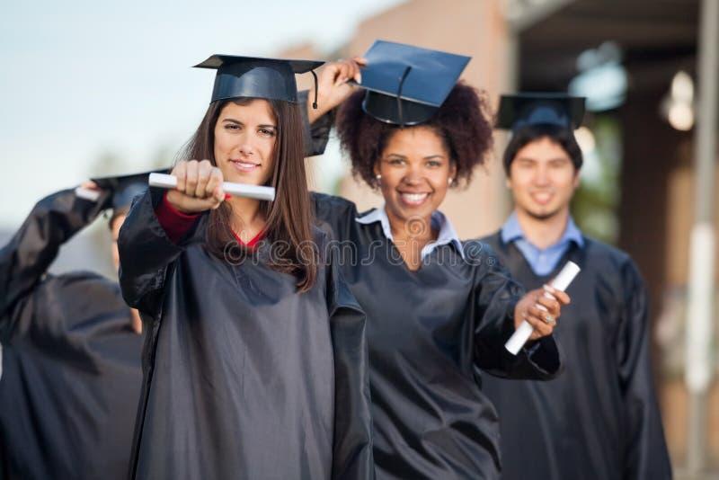 Étudiantes montrant des certificats sur l'université photos libres de droits