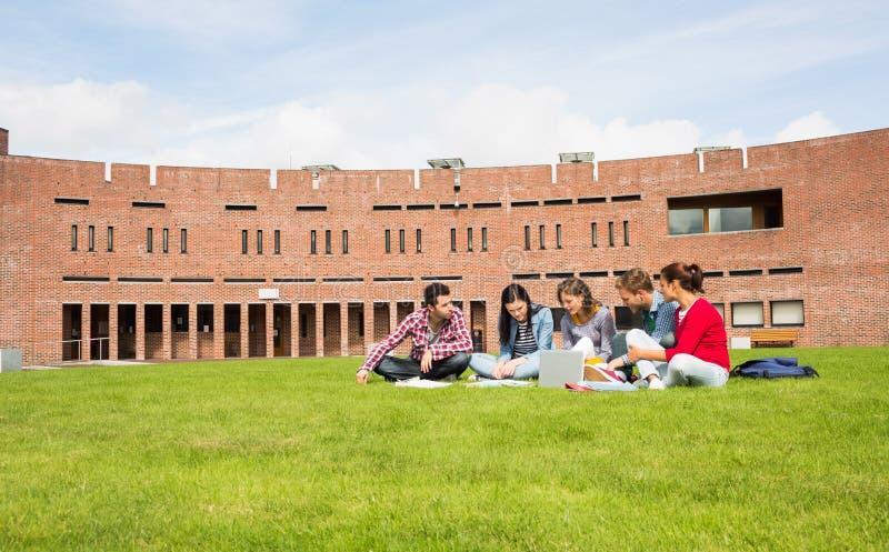 Étudiants à l'aide de l'ordinateur portable dans la pelouse contre le bâtiment d'université photo stock