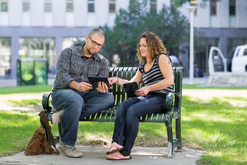 Étudiants à l'aide de la Tablette de Digital sur le banc au campus image libre de droits