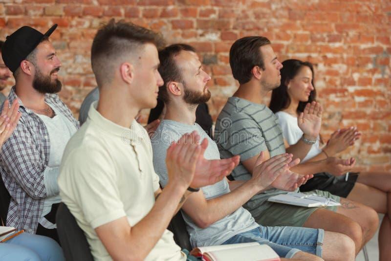 Étudiants écoutant la présentation dans le hall à l'atelier d'université photo libre de droits