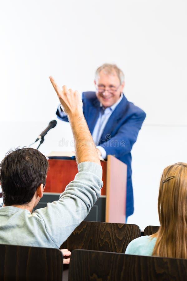 Étudiants écoutant le professeur d'université photos stock