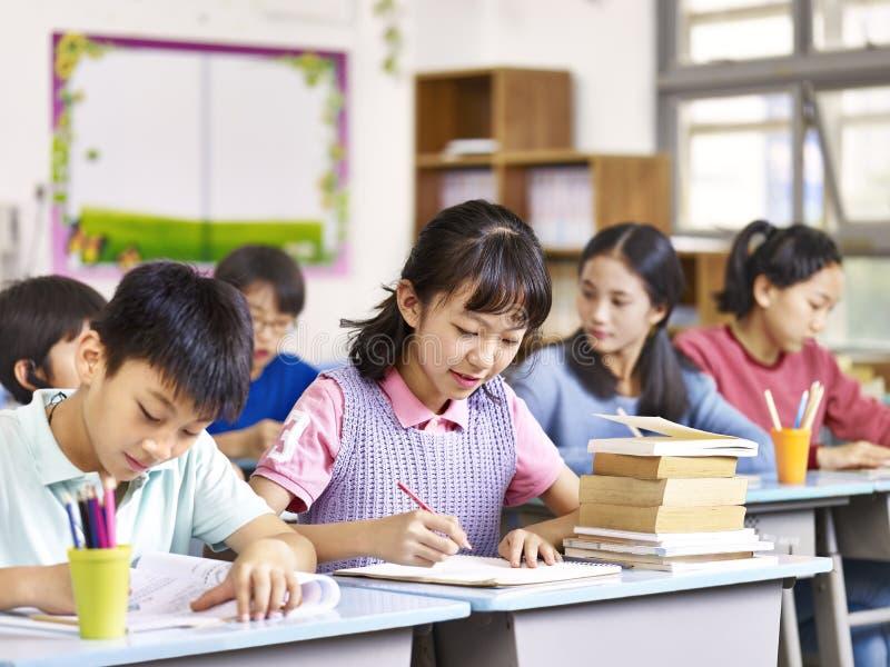 Étudiants élémentaires asiatiques dans la classe photo stock