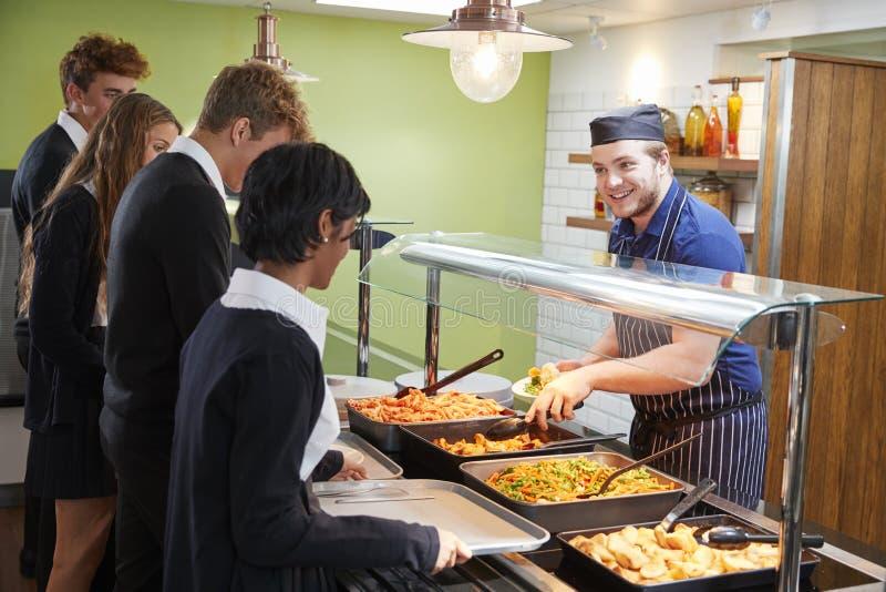 Étudiants adolescents étant servis le repas dans la cantine scolaire photos stock